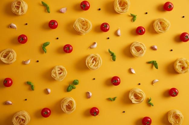 Фотография сырых макаронных гнезд, лежащих вокруг съедобных красных помидоров, чеснока, перца, базилика на желтом фоне. готовим сытную еду. итальянская традиционная кухня. большой выбор товаров