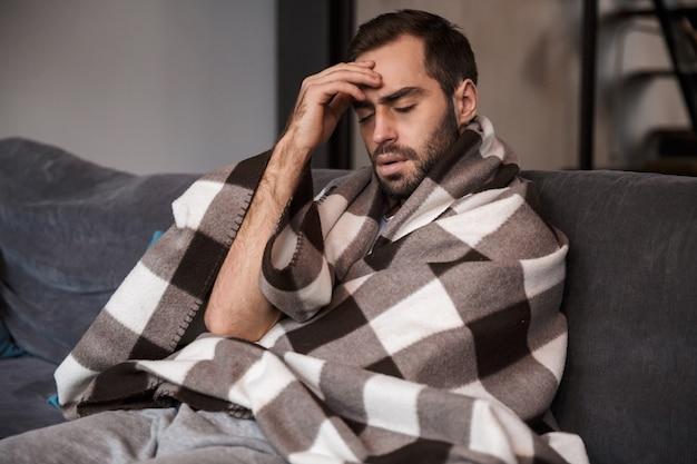 불행한 남자 30 대의 사진은 담요에 싸여 있고 아파트에서 소파에 앉아있는 동안 아프다.