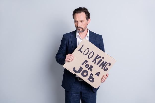 Фотография несчастного грустного напряженного работника в возрасте зрелого парня-неудачника делового человека, финансового кризиса, потерявшего работу, удерживайте картонный плакат, поиск работы, спросите, помогите рынку труда, носить костюм, изолированный серый фон