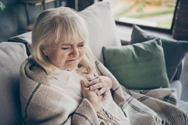 Фотография несчастной седой пожилой бабушки, держащей грудную зону, сердечные трудности, боится сердечного приступа, сидя на диване, на диване, покрытом клетчатым одеялом, в гостиной в помещении