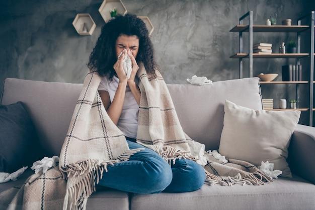インフルエンザに苦しんでいる不健康な黒い肌の波状の女性の写真は、どこでも冷たいくしゃみをする紙ナプキンを捕まえました。