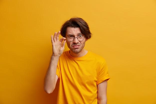 感動しない不機嫌な大人の男性の写真は、非常に小さなオブジェクトを形作り、小さな何かを示し、見栄えがよく、丸い透明な眼鏡をかけ、黄色の壁に隔離されています