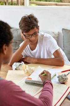 認識できない女性の写真が座って、ノートにペンでポイントし、弟に資料を説明し、職場でポーズをとり、財務報告を手伝い、アシスタントを与え、タスクを説明します