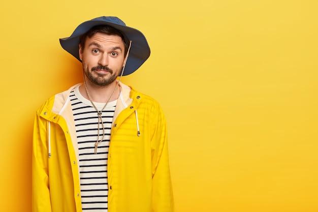 На фото небритый мужчина отдыхает, идет на рыбалку в выходные, носит шляпу и защитный плащ, выглядит без сюрпризов, позирует на желтой стене, свободное пространство
