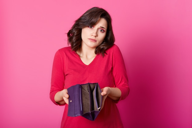 手で開かれた財布と動揺のブルネットの写真。美しい悲しい女性は肩を絞って、購入の支払い方法を知りません。魅力的な女の子はピンクの壁に赤いジャンパースタンドを着ています。