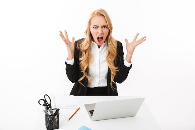 Фото расстроенной бизнес-леди, сидящей за столом и работающей на ноутбуке, изолированные