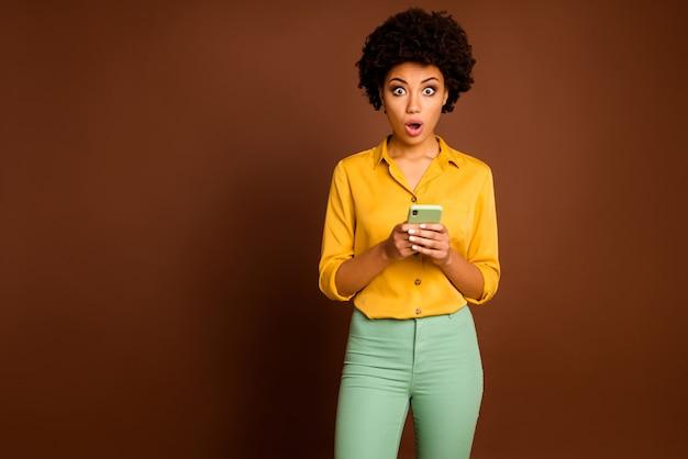 Фотография расстроенной темнокожей волнистой дамы, держащей телефонное приложение, фрилансер с открытым ртом, читающая ужасные негативные комментарии, в желтой рубашке, зеленые штаны, изолированные коричневого цвета