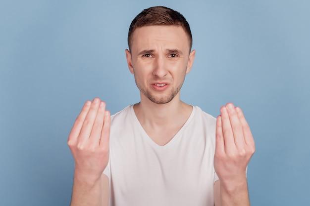 動揺の写真は、青い色の背景に孤立してイライラした若い茶色の髪の男の問題を不快にさせる