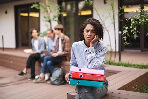 カラフルなフォルダーと悲しいことにベンチに座っている動揺した女性の写真