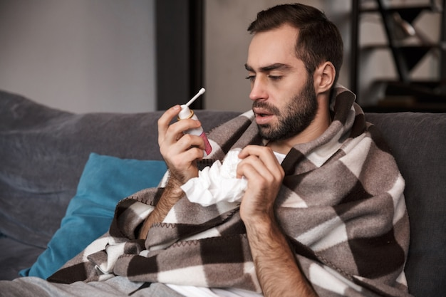 Фотография расстроенного мужчины 30 лет, завернутого в одеяло, у которого температура и который болеет, сидя на диване в квартире Premium Фотографии