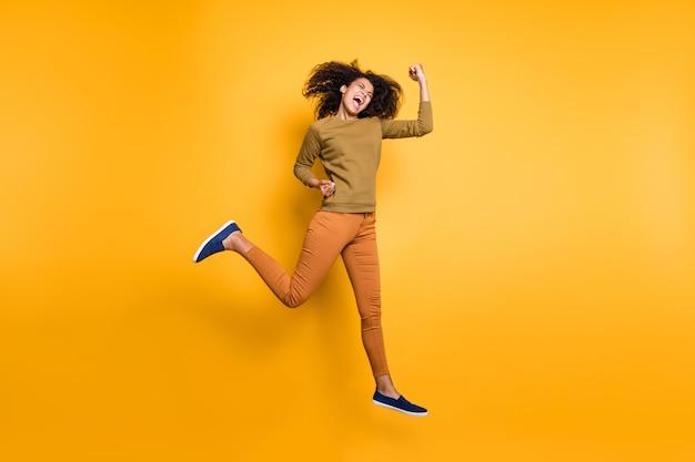 オレンジ色のズボンのズボンの履物を身に着けている緊急の巻き毛の波状のスタイルのトレンディな陽気な美しいガールフレンドの写真鮮やかな色の背景の上に孤立して実行されている緑のセータージャンプ
