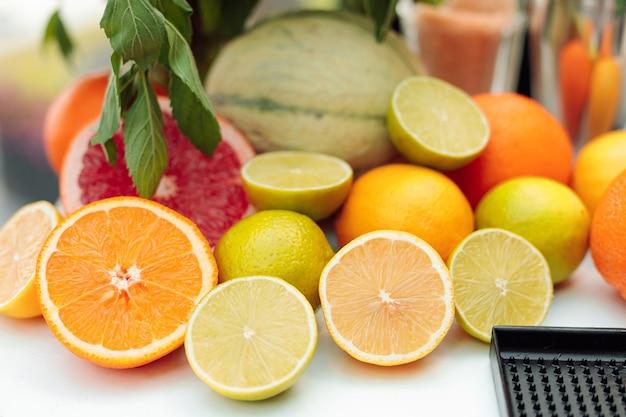 新鮮なミントの緑の葉を背景に、半分にカットされたさまざまな柑橘系の果物の写真がテーブルに横たわっています。デトックスコンセプト。閉じる。