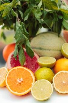 ミントの緑の葉を背景に、半分にカットされたさまざまな柑橘系の果物の写真がテーブルに横たわっています。デトックスコンセプト。閉じる