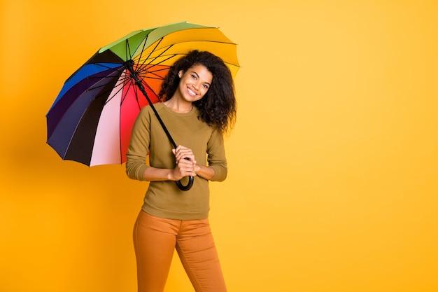 Фотография волнистой веселой милой случайной очаровательной очаровательной зубастой сияющей девушки, прячущейся от дождя под зонтиком, изолированной на ярком цветном фоне