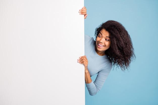波状の陽気なポジティブな素敵なかわいいガールフレンドの写真は、歯のように孤立した青いパステルカラーの背景に笑みを浮かべてその後ろに隠れている白い空白のバナーの空のスペースを見て