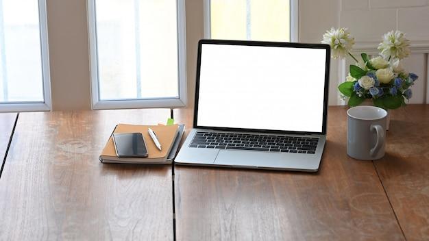 白い空白の画面のラップトップ、コーヒーカップ、ノートブック、ペン、鉢植えの植物の写真を背景として、窓からの光で木製のテーブルの上に置きます。