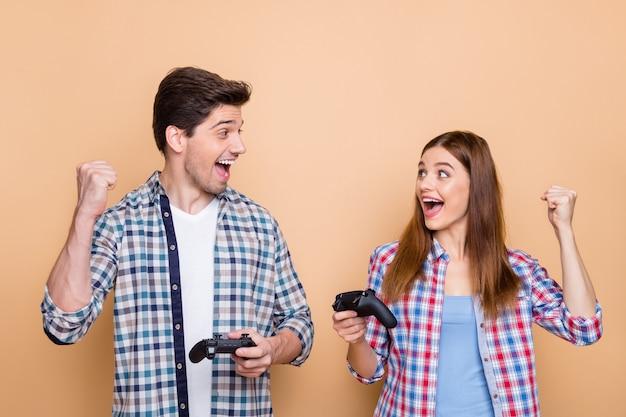 Фотография белой веселой позитивной красивой стильной модной пары из двух человек, играющих на playstation с джойстиками, выигравших игру в команде, изолировала бежевый пастельный цвет фона