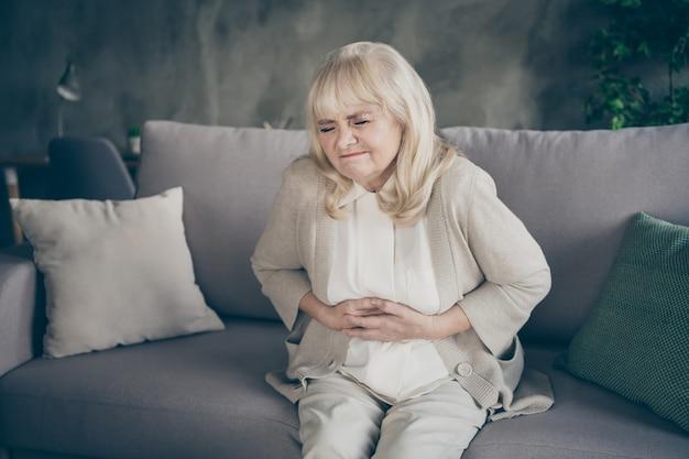 Фотография седой пожилой бабушки в отчаянии, держащей живот, страдающей гормональным дисбалансом, сидящей на диване, покрытом пледом, гостиной в помещении