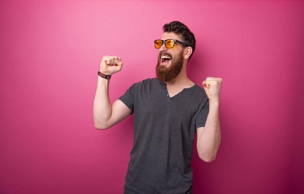 ピンクの背景の上に上がった手で祝う勝者のひげを生やした男の写真