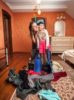 Фотография женщины, обнимающей маленькую девочку в маске и трубке, стоящей в чемодане