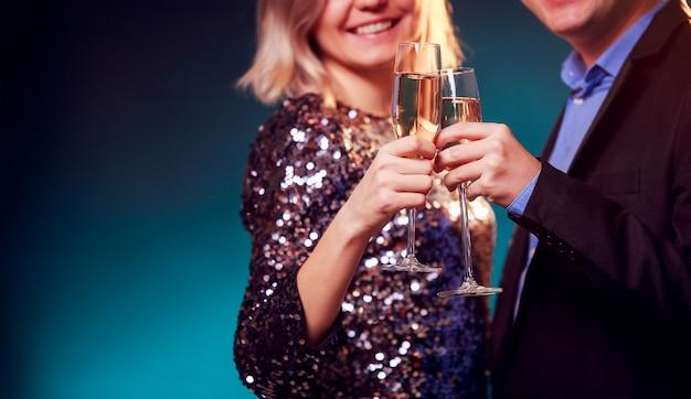 鮮やかなドレスを着た女性と青い背景にシャンパンとワイングラスを持つ男性の写真