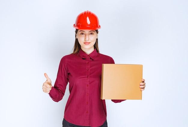 Фото женщины в красном шлеме держа картонную коробку и давая большие пальцы руки вверх.