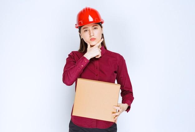Фото женщины в красном шлеме держа картонную коробку на белой предпосылке.
