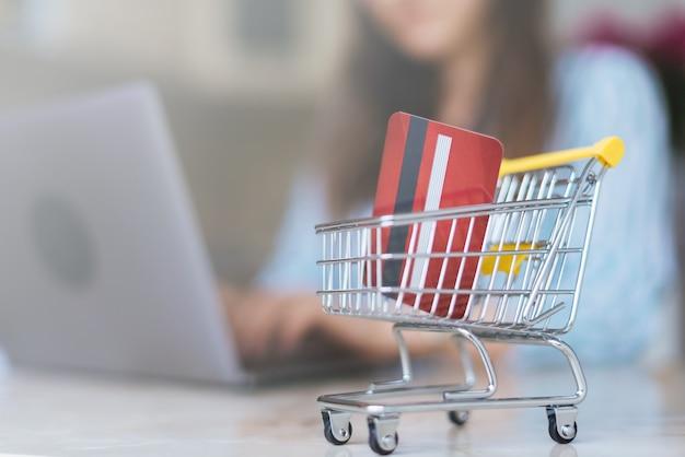 Фото женщины делая покупки онлайн с тележкой вагонетки.