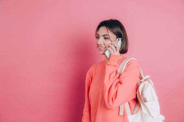 Фотография женщины, улыбающейся во время разговора на смартфоне, изолированной на розовом фоне