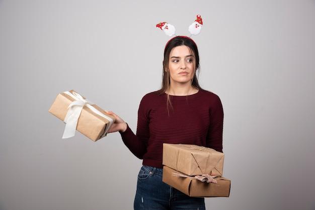 머리띠를 착용하고 선물을 들고 있는 여성의 사진.