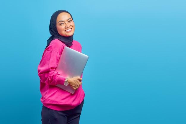 女性の写真アジアは青い色の背景に分離されたラップトップウェアピンクのセーターを保持します