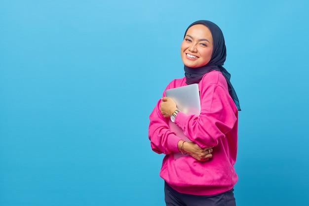 女性の写真アジアはラップトップを着用ピンクのセーターを保持します