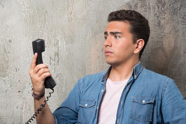 전화로 얘기하고 의자에 앉아 궁금해하는 남자의 사진. 고품질 사진