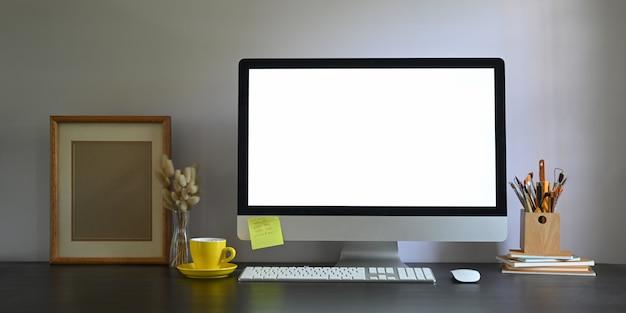 Фото монитора компьютера пустого экрана workspace кладя на рабочий стол и окруженный картинной рамкой, держателем карандаша, стогом книг, беспроволочной мышью, клавиатурой, кофейной чашкой и дикой травой в вазе.
