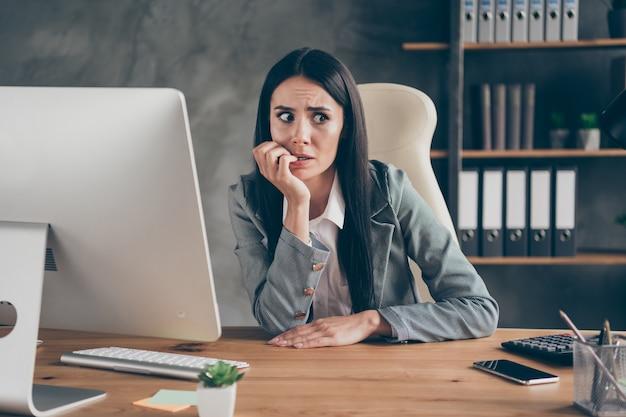 걱정스러운 겁에 질린 소녀가 책상에 앉아 원격 컴퓨터로 손톱을 물어뜯는 사진은 회사 위기 파산에 대한 두려움을 느끼고 직장 워크스테이션에서 블레이저 재킷 슈트를 입는다