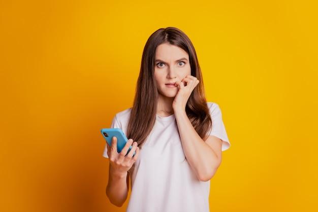 노란색 바탕에 흰색 티셔츠를 입고 전화기를 들고 있는 걱정스러운 여성이 손톱을 물어뜯는 사진