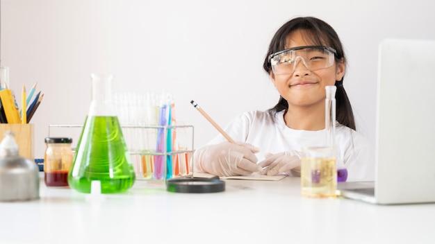 Фото молодой очаровательной девушки, написание химического результата на книге во время проведения научного эксперимента
