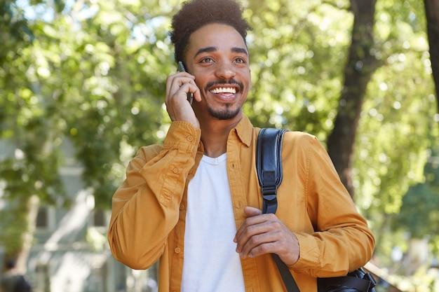 公園を歩いて、友人と電話で話し、笑って一日を楽しんでいる若いアフリカ系アメリカ人の喜んでいる男の写真。