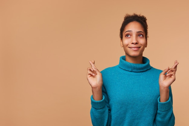 Фотография молодой афро-американской женщины в синем свитере с вьющимися темными волосами. глядя вверх, скрестив пальцы и загадывая желание. изолированные на фоне biege с copyspace.