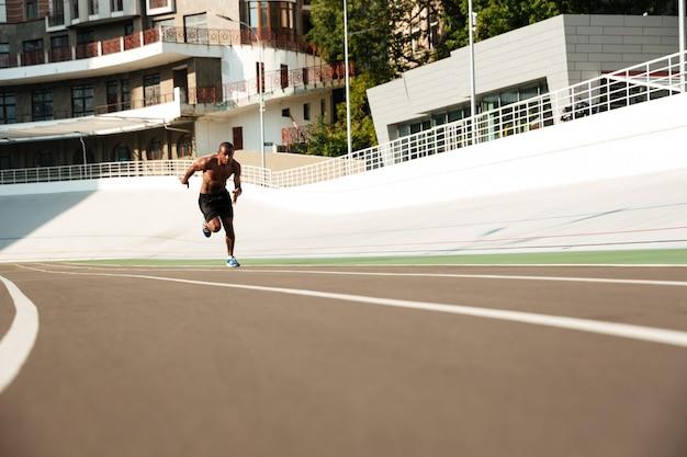 Фотография молодого африканского человека спортсмена, бегущего на беговой дорожке на открытом воздухе