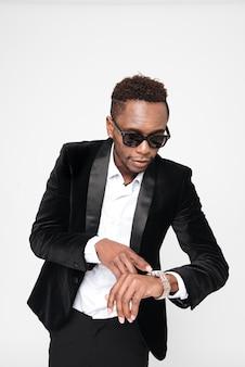 Фото молодого африканского бизнесмена в очках смотря часы. изолированные на белом фоне.