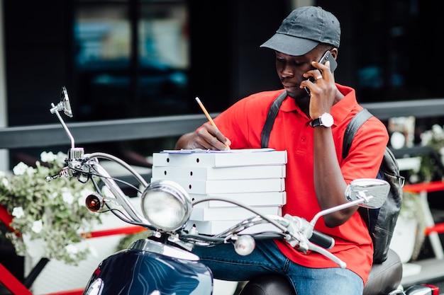 若いアフリカ人の写真は電話で注文を受け付け、ピザの入ったバイクの収納ボックスに書き込みます。都会の場所。
