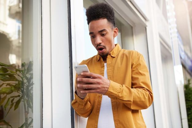 На фото молодой изумленный темнокожий парень в желтой рубашке идет по улице, держит телефон, читает невероятные новости, с широко открытыми глазами и ртом, выглядит ошеломленным.