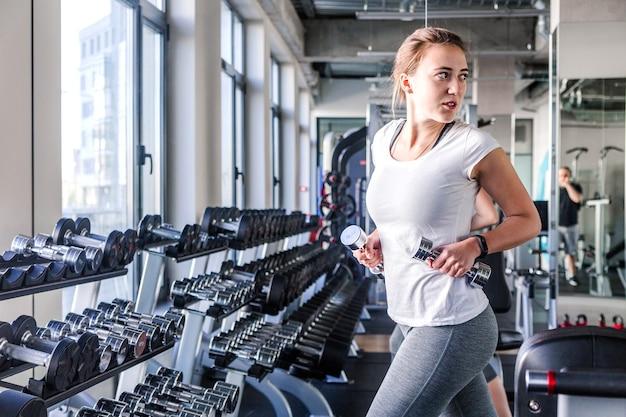 Фото молодой и красивой женщины, тренирующейся с гантелями в тренажерном зале