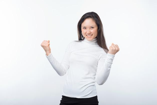 Фото молодой азиатской очаровательной женщины празднуя над белой предпосылкой.