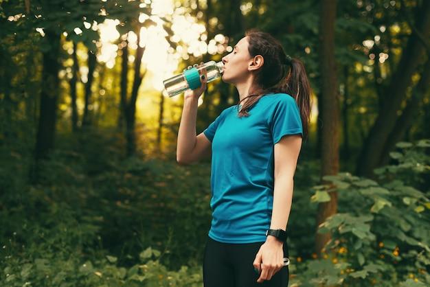 Фотография молодой спортсменки в спортивной одежде с питьевой водой во время тренировки в лесу