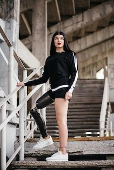 Фотография молодой спортивной девушки-инвалида с протезом ноги в спортивной одежде, идущей с улыбкой на открытом воздухе