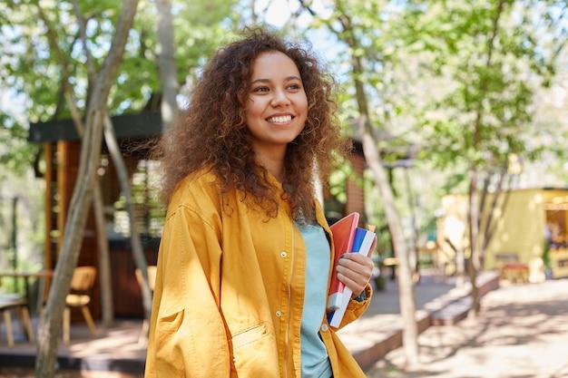 若い魅力的な浅黒い肌の巻き毛の学生の女性の写真は、カフェテラスを歩いて、黄色いコートを着て、広く笑顔で、人生を楽しんでいます。