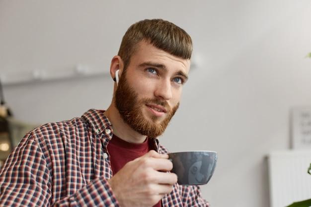 Фотография молодого привлекательного имбирного бородатого мужчины, держащего серую кофейную чашку, мечтательно смотрит вверх и наслаждается кофе в простой одежде.
