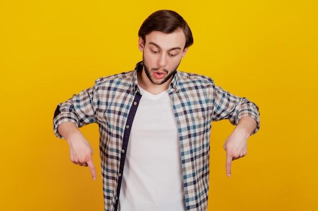 若い魅力的な男の写真は、黄色の背景の上に分離された注意を広告の注意を広告する空のスペースの指を見て驚いています